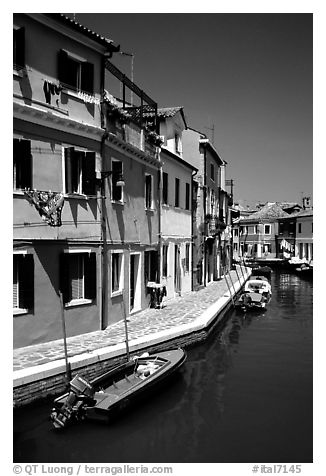 Canal surrounded by houses painted  a multitude of bright colors, Burano. Venice, Veneto, Italy (black and white)