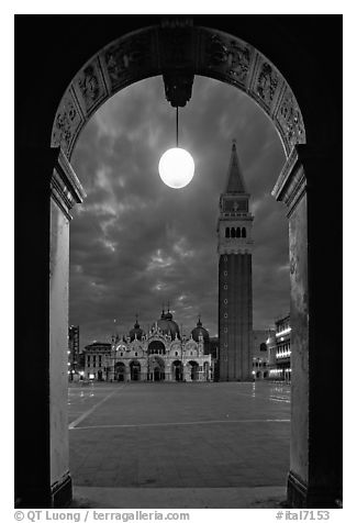 Campanile and Piazza San Marco (Square Saint Mark) seen from arcades at night. Venice, Veneto, Italy (black and white)