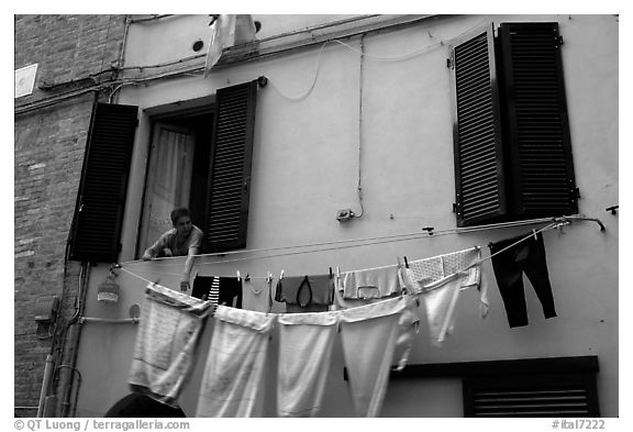 Woman hanging laundry. Siena, Tuscany, Italy (black and white)