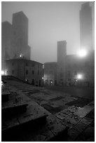 Piazza del Duomo at dawn in the fog. San Gimignano, Tuscany, Italy ( black and white)