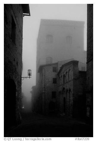 Street and medieval tower at dawn in the fog. San Gimignano, Tuscany, Italy (black and white)