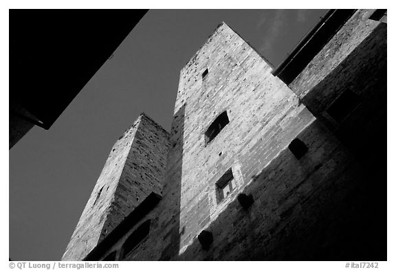 Medieval tower seen from the street, early morning. San Gimignano, Tuscany, Italy (black and white)