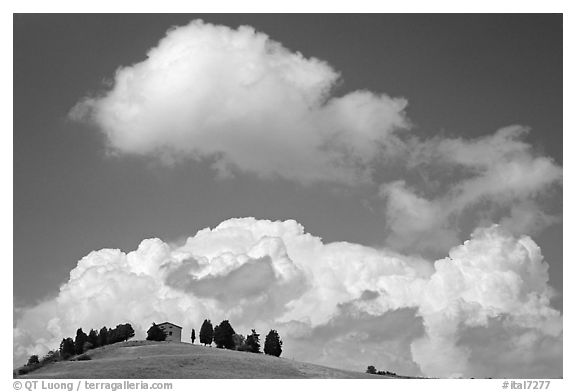 Fluffy clouds above ridge with cypress trees and house. Tuscany, Italy (black and white)