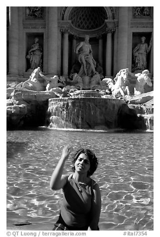 Tourist tosses a coin over her shoulder in the Trevi Fountain. Rome, Lazio, Italy (black and white)