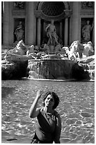 Visitor tosses a coin over her shoulder in the Trevi Fountain. Rome, Lazio, Italy (black and white)