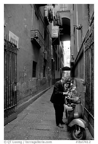 Man locking his motorbike in a side street. Naples, Campania, Italy (black and white)