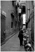 Man locking his motorbike in a side street. Naples, Campania, Italy ( black and white)