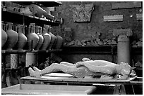 Artifacts found during the excavations, including a petrified man. Pompeii, Campania, Italy (black and white)