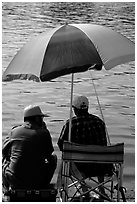 Men fishing under an colorful sun unbrella,  Agropoli. Campania, Italy (black and white)