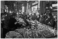 Unusual street foods on busy shopping street. Seoul, South Korea (black and white)