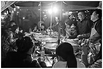 People eating noodles in a tent at night. Seoul, South Korea (black and white)