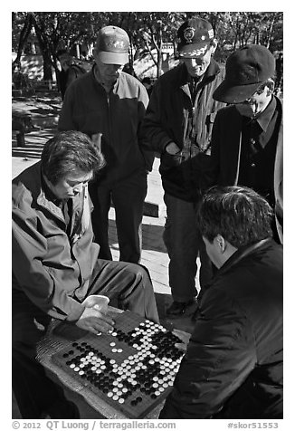 Elderly men play game of baduk (go). Seoul, South Korea (black and white)