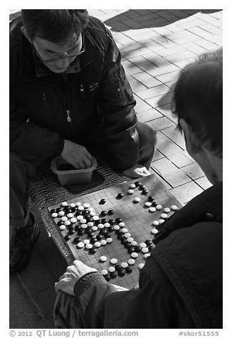 Pondering moves in go (baduk) game. Seoul, South Korea (black and white)