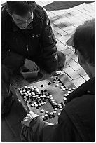 Pondering moves in go (baduk) game. Seoul, South Korea ( black and white)