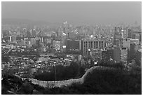 Old fortress wall and high-rises at dusk. Seoul, South Korea ( black and white)