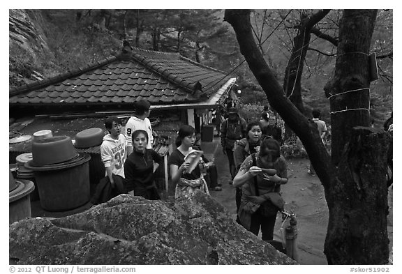 Hikers drinking from foundtain at Sangseonam hermitage, Namsan Mountain. Gyeongju, South Korea (black and white)