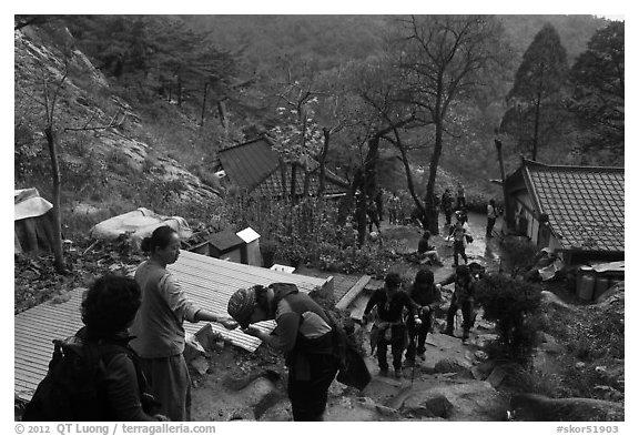 Hikers receiving sacred bread at Sangseonam hermitage, Mt Namsan. Gyeongju, South Korea (black and white)