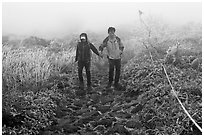 Couple hiking holding hands in fog. Jeju Island, South Korea ( black and white)
