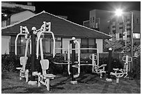 Exercise equipment in yard at night, Seogwipo. Jeju Island, South Korea (black and white)