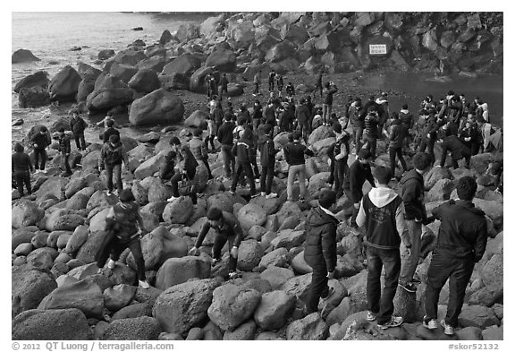 Crowd on rocky beach, Seogwipo. Jeju Island, South Korea (black and white)