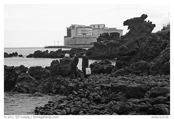 Businessmen on shore near Yongduam Rock, Jeju-si. Jeju Island, South Korea (black and white)