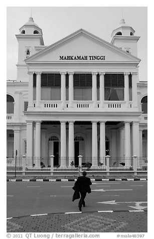 Man in suit crossing streets towards court building. George Town, Penang, Malaysia (black and white)