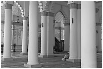 Man in prayer inside Masjid Kapitan Keling mosque. George Town, Penang, Malaysia ( black and white)