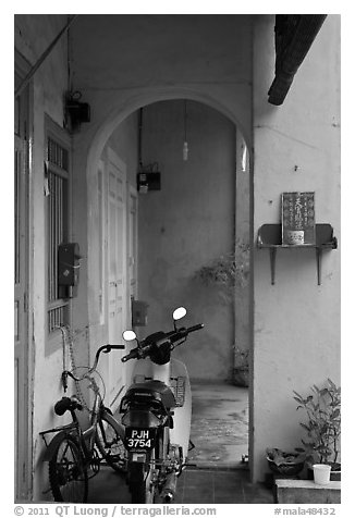 Motorcycle and altar outside townhouse. George Town, Penang, Malaysia (black and white)