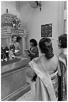 Holy man distributes fire to women, Sri Mariamman Temple. George Town, Penang, Malaysia (black and white)