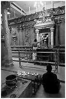 Holy man tends to altar, Hindu temple. George Town, Penang, Malaysia (black and white)