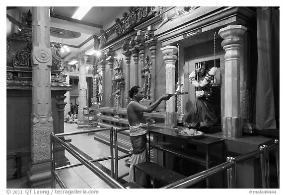 Holy man lights altar inside Sri Mariamman Temple. George Town, Penang, Malaysia (black and white)