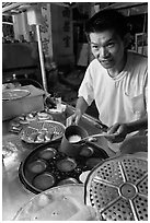 Man preparing mini-pancakes. George Town, Penang, Malaysia ( black and white)