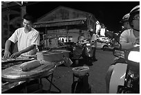 Man preparing food as people wait on motorbike. George Town, Penang, Malaysia (black and white)