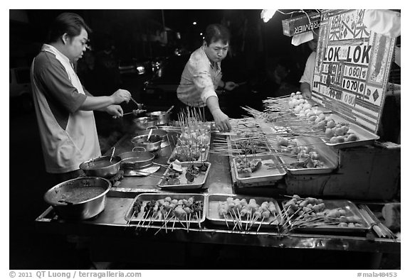 Men arranging skewers on hawker stall. George Town, Penang, Malaysia