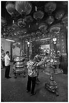 Worshiping inside goddess of Mercy temple. George Town, Penang, Malaysia (black and white)