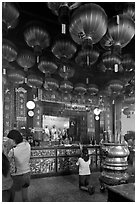 Woman in prayer, altar and lanters, Kuan Yin Teng temple. George Town, Penang, Malaysia (black and white)