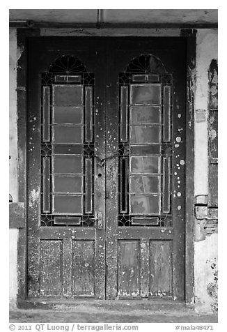 Old green door locked with chain. George Town, Penang, Malaysia (black and white)