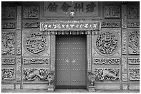 Red door and slate carved wall, Hainan Temple. George Town, Penang, Malaysia (black and white)