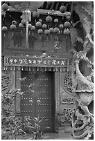 Red paper lanters, door, and stone carved wall, Hainan Temple. George Town, Penang, Malaysia (black and white)