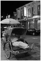 Driver taking nap in trishaw at night. George Town, Penang, Malaysia (black and white)