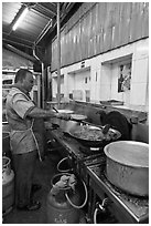 Man frying food in large pan. George Town, Penang, Malaysia (black and white)