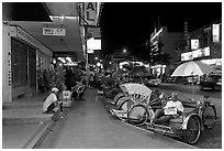 Cycle rickshaws lined on street at night. George Town, Penang, Malaysia ( black and white)