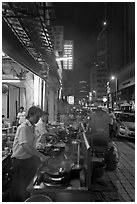 Cooks preparing food on Chinatown street at night. Kuala Lumpur, Malaysia ( black and white)