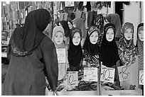 Woman in apparel store with islamic headscarves for sale. Kuala Lumpur, Malaysia (black and white)