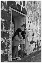 Malay girls exit on St Paul church doorway. Malacca City, Malaysia (black and white)