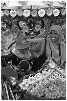 Mother and child riding decorated trishaw. Malacca City, Malaysia (black and white)