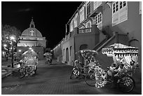 Illuminated trishaws on Town Square at night. Malacca City, Malaysia (black and white)