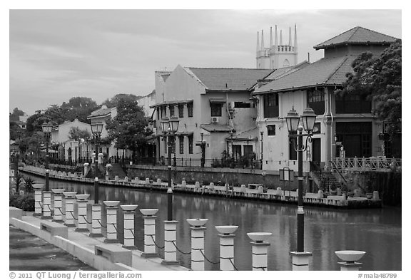 Lamps, riverside houses and St Peters Church towers. Malacca City, Malaysia (black and white)