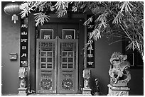 Chinese house entrance with lion sculpture and lanterns. Malacca City, Malaysia (black and white)