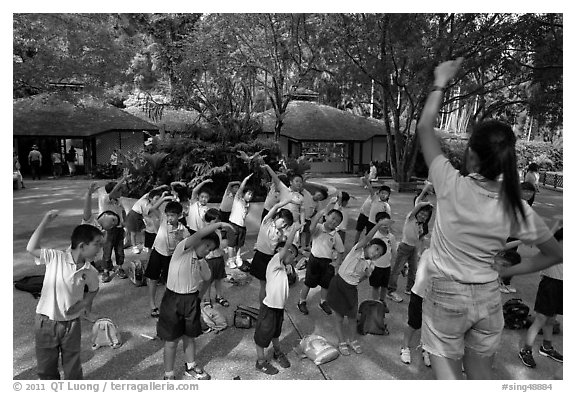 Schoolchildren doing gymnastics in  Singapore Botanical Gardens. Singapore (black and white)